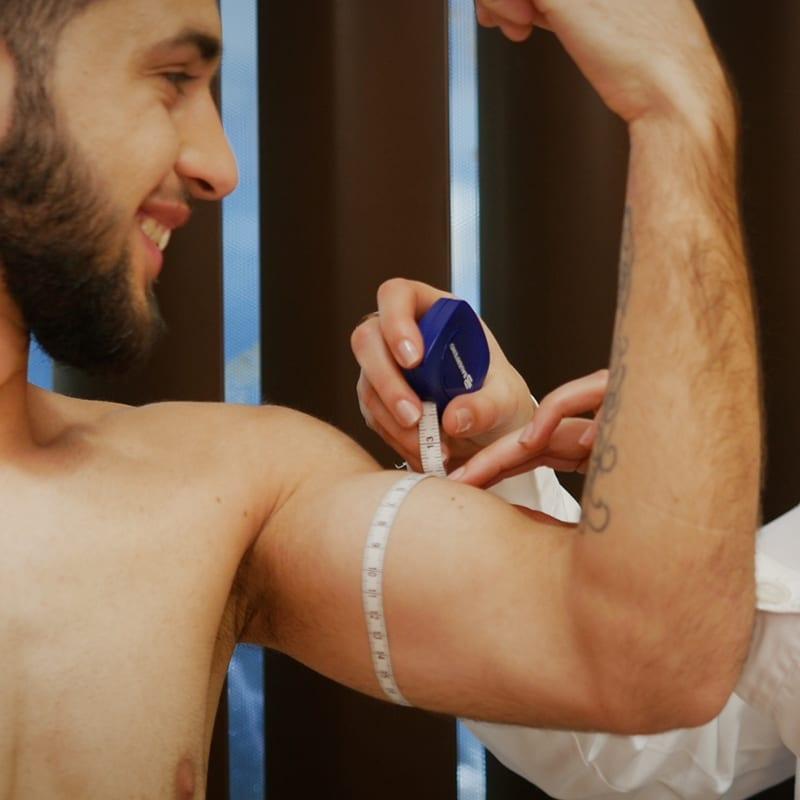 Homem a tirar medida do biceps